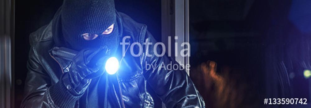 Einbrecher mit Brecheisen und Taschenlampe